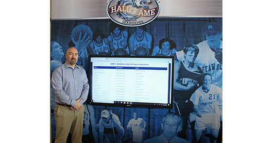 Matt Richards, Associate Dean of Students and Director of Athletics, in front of the interactive Athletics Hall of Fame inside the HUB lobby.